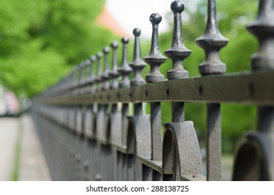 Vanishing line of wrought-iron fence spikes