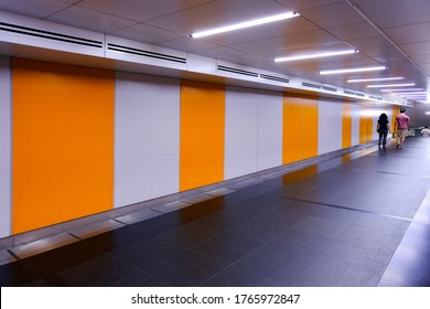 Vanishing perspective view of pedestrian underpass tunnel with empty walls / blank billboard spaces. Visual for ad placements; presentation display; advertising OOH mockup / mock up.