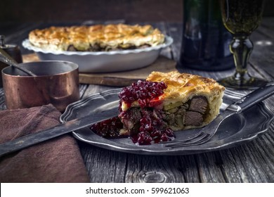 Vanison Pie with Cranberry Relish as close-up on a pewter plate