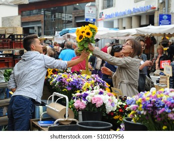 VANNES, FRANCE - AUGUST 2016 - MARKET IN VANNES, FRANCE: A woman buys flowers at a market in Vannes, France.