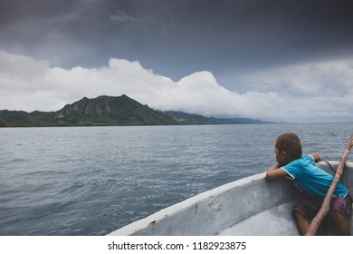 Vanua Levu, Fiji - February 4, 2017 - Young Fijian Boy Child Resting Heading Looking Over Fiberglass Boat to Mountains Under Clouds Across Pacific Ocean In Distance