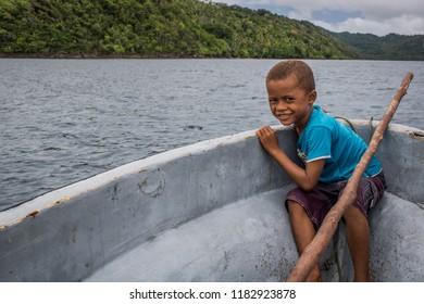 Vanua Levu, Fiji - February 4, 2017 - Young Fijian Boy Child Smiling On Fiberglass Boat Mountain Coast Across Pacific Ocean In Distance