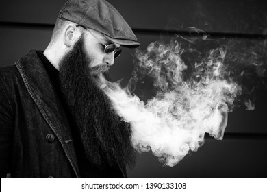 Vape bearded man. An adult man with a very long beard in a cap and sunglasses smokes an electronic cigarette on a sunny day outside. Bad habit that is harmful to health. Black and white.