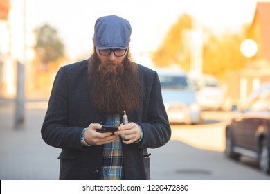 8ec724e2d90 Vape bearded man in real life. Portrait of young guy with large beard in  glasses