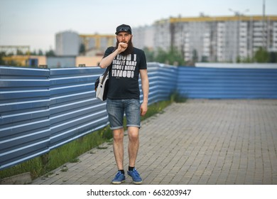 Vape bearded man in real life. Portrait of young guy with large beard in a cap and sunglasses vaping an electronic cigarette near the blue fence.