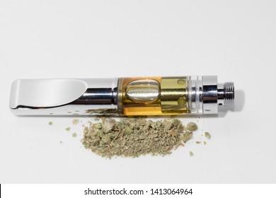 Vape Cartridge and Marijuana Bud on White Background. Vaping Cannabis with Dab Pen
