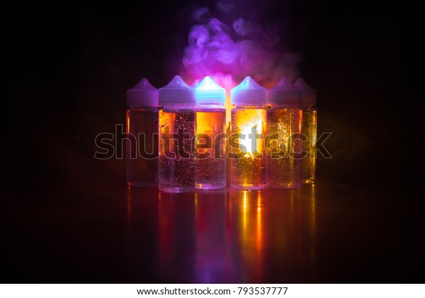 Vape concept. Smoke clouds and vape liquid bottles on dark background. Light effects. Selective focus
