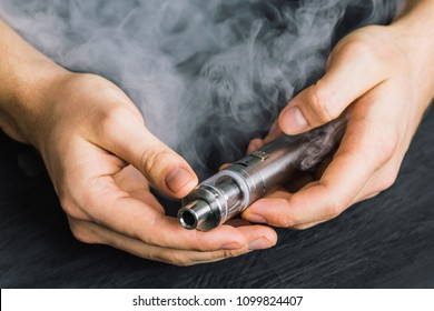 vape device at cloud of vapor background. Vape concept, toned Man hand shows vape device at cloud of vapor background. Vape co
