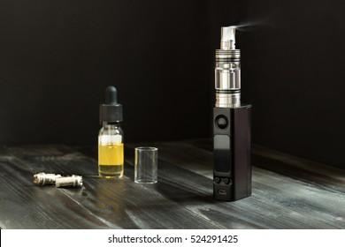 Vape or e-cigarette. Vaping set on the wooden table.
