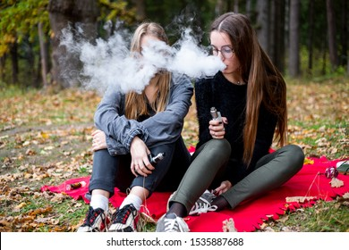 Vape lgbt teenagers. Bisexual lesbian young caucasian teenage girls in casual clothes vape electronic cigarette on the street in the park in the autumn evening. Bad habit.