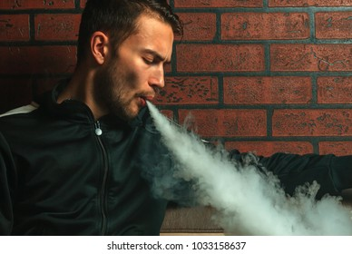 Vape man. Indoor portrait of a young handsome white guy letting of steam from an electronic cigarette. Vaping process. Close up.