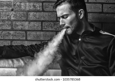 Vape man. Indoor portrait of a young handsome white guy letting puffs of steam from an electronic cigarette. Vaping process. Black and white. Close up.