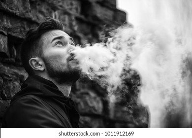 Vape man. Photo of a handsome young white guy with modern haircut in the black clothes vaping and letting off steam from an electronic cigarette near old destroyed brick wall. Black and white photo.