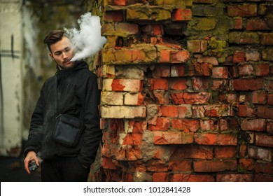 Vape man. Photo of a handsome young white guy with modern haircut in the black clothes vaping and letting off steam from an electronic cigarette near