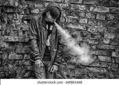 Vape man. Photo of a handsome young white guy in the hood vaping and letting off steam from an electronic cigarette near old destroyed brick wall. Black and white photo. Lifestyle.