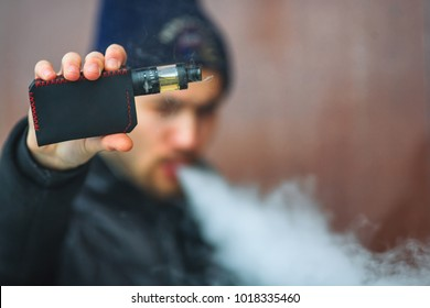 Vape man. Portrait of a handsome young white guy in black waistcoat and modern cap vaping an electronic cigarette and letting out puffs of steam