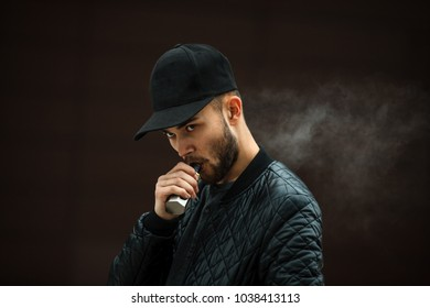 Vape man. Portrait of a handsome young white guy in a modern black cap vaping an electronic cigarette opposite the futuristic urban background.