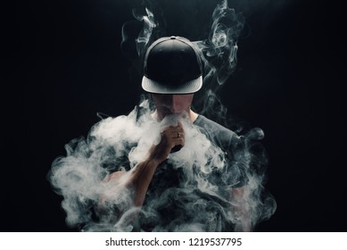 Vape man. Portrait of a handsome young white guy in a modern black cap vaping and letting off puffs of steam from an electronic cigarette