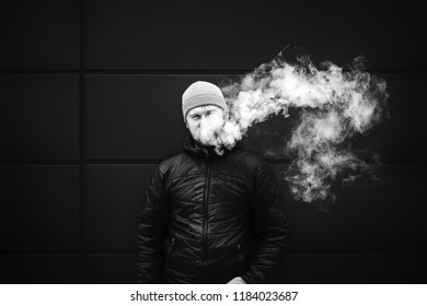 Vape man. Young bearded white guy in the cap is smoking an electronic cigarette and letting off the steam. Bad habit. Black and white.