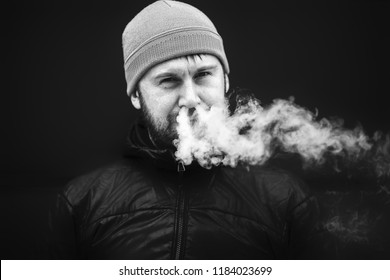 Vape man. Young bearded white guy in the cap is smoking an electronic cigarette and letting off the steam. Bad habit. Black and white. Close up.