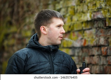 Vape man. Young caucasian white guy in black jacket smoking and letting off steam from an electronic cigarette near old destroyed brick wall in the autumn. Bad habit. Vaping activity. Lifestyle.