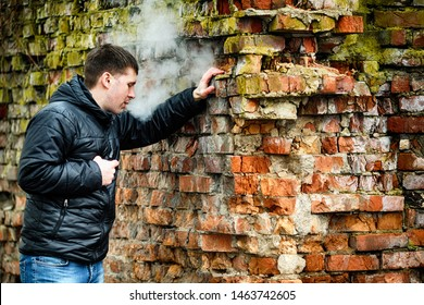 Vape man. Young caucasian white guy in black jacket smoking and letting off steam from an electronic cigarette near old destroyed red brick wall in the autumn. Bad habit. Vaping activity. Lifestyle.