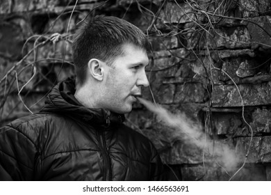 Vape man. Young caucasian white guy in black jacket smoking and letting off steam from an electronic cigarette near old destroyed brick wall in the autumn. Bad habit. Vaping activity. Black and white