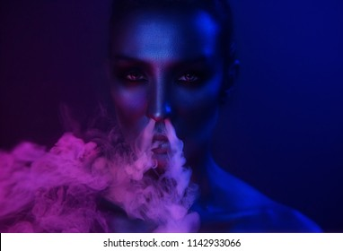 Vape Party. Beautiful Sexy Young Woman with glamorous mystical makeup vaping in Nightclub (exhaling smoke). Girl smoking in Club. Blue mystic smoke. Halloween night.