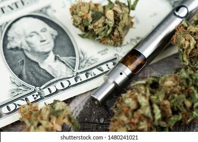 Vape Pen. Cannabis Marijuana Vaporizer. Medical Marijuana Buds with pen vaporizer on One Dollar bill. CBD and THC vaping products. Vape CBD or THC Oil. Vaping Marijuana and Cannabis. Vaporizer