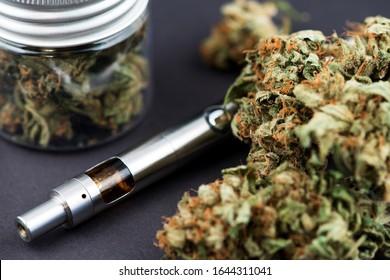 Vape Pen. Cannabis Marijuana Vaporizer. Cannabis Marijuana Buds and pen vaporizer close up image. CBD and THC vaping products. Vape CBD or THC Oil. Vaping Marijuana and Cannabis. Vaporizer Marijuana