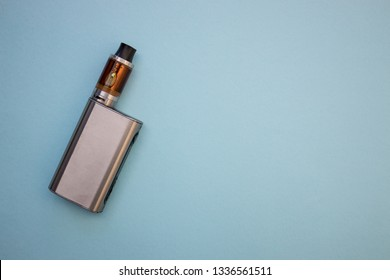 Vape pen metal electronic cigarette with vaping blue background top view