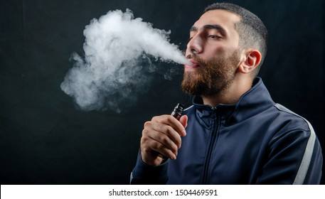 vape and smoke vape electronic e-cigarette or e-cig by a young man with smoke clouds over a black background.