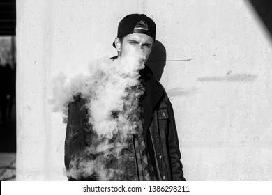 Vape teenager. Portrait of young handsome guy smoking an electronic cigarette near the wall on the street in the spring. Bad habit that is harmful to health. Vaping activity. Black and white.