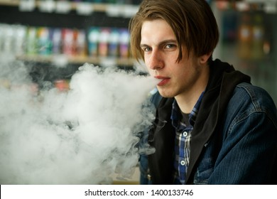 Vape teenager. Portrait of young handsome guy smoking an electronic cigarette in the vape bar. Bad habit that is harmful to health. Vaping activity. Close up.