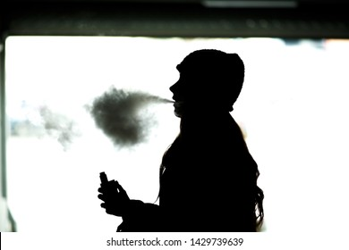 Vape teenager. Silhouette of a young girl in a hat smoking an electronic cigarette. Harmful habit that is harmful to health. Vaping activity.