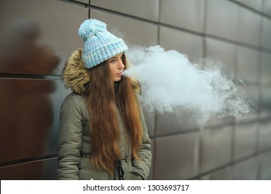 Vape teenager. Young pretty white girl smoking an electronic cigarette opposite modern brown background on the street in the winter. Close up.