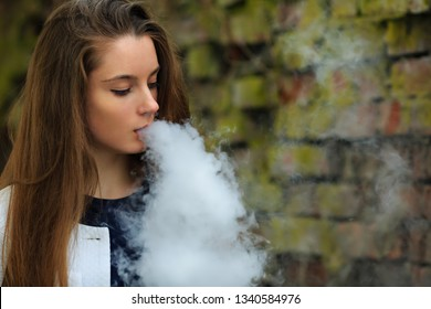 Vape teenager. Young pretty white girl in white cardigan smoking an electronic cigarette opposite destroyed brick wall on the street in the spring. Bad habit.