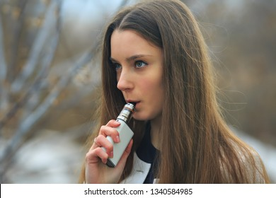 Vape teenager. Young pretty white girl smoking an electronic cigarette on the street in the autumn. Bad habit.