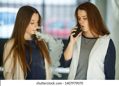 Vape teenagers. Two young cute girls in casual clothes smoke electronic cigarettes outdoors in the street in summer day. Bad habit that is harmful to health. Vaping activity.