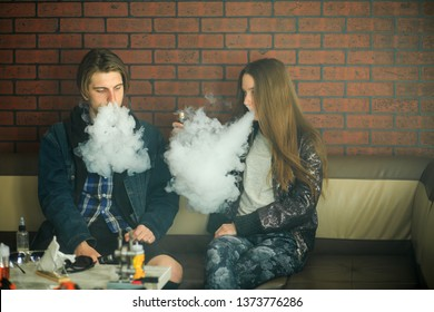 Vape teenagers. Young cute girl in sunglasses and young handsome guy smoke an electronic cigarettes in the vape bar. Bad habit that is harmful to health. Vaping activity.