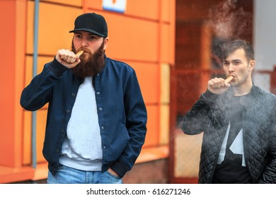 Vape. Two young people stand and smoke electronic cigarettes in the street on a cloudy day. Lifestyle.