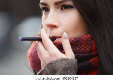 Vaper girl smokes electric cigarette device.Sad young brunette woman smoking vaporizer with glycerin eliquid.Stop smoking,start vaping.Portrait of beautiful young female smoker