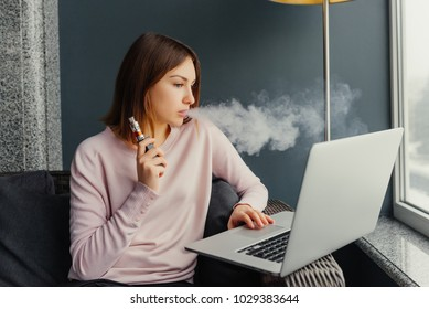 Vaping. Beautiful brunette smoke electronic cigarette in restaurant and working on her laptop. Vapor concept. Electronic cigarette with working
