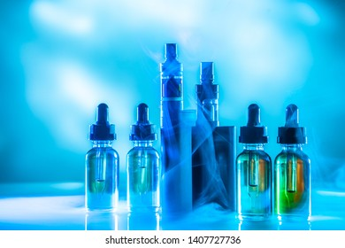 The vaping concept. Vaping set on blue background with smoke. Vapes and bottles with filling liquid. Electronic devices for smoking. Smoking gadgets. E-cigs.
