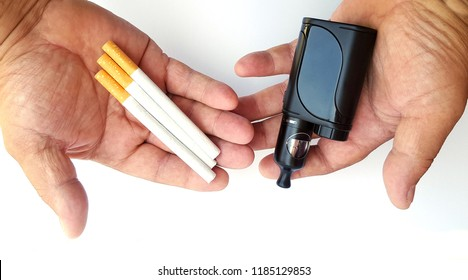 Vaping device and cigarettes in the man's hand, concept of choosing the type of cigarette