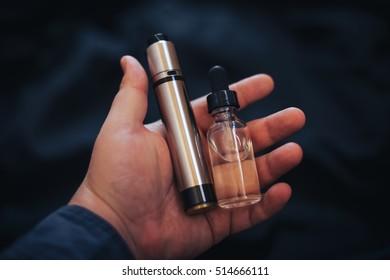Vaping device in in the man's hand. Electronic cigarette, vape. Mech mod, RDA, E-juice bottle