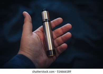 Vaping device in in the man's hand. Electronic cigarette, vape. Mech mod, sub-ohm