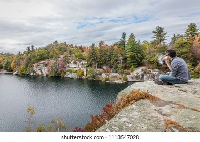 Vaping and enjoying the scenery overlooking the Minnewaska Lake surrounded by bright fall foliage on a partly cloudy afternoon