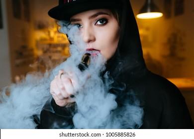 Vaping girl. Young hipster woman vape e-cig at the vapeshop. Hip-hop style. Closeup.