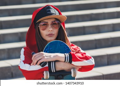 Vaping girl. Young woman with skateboard vape e-cig. Pretty young female in black hat, red clothing vape ecig, vaping device at the sunset. Toned image. Hip-hop style.